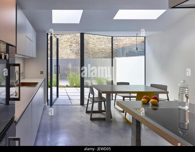Kitchen un use, adjustable height work-top, joining the table to the work-top for lunch. The Slide Return, London, - Stock Image