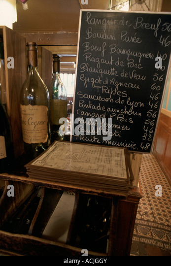 Restaurant blackboard with courses and prices against mirror bottle of cognac - Stock Image