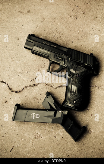 Gun and ammo clip on the ground - Stock Image