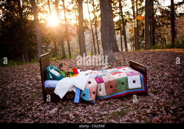 Young boy in bed in forest - Stock-Bilder