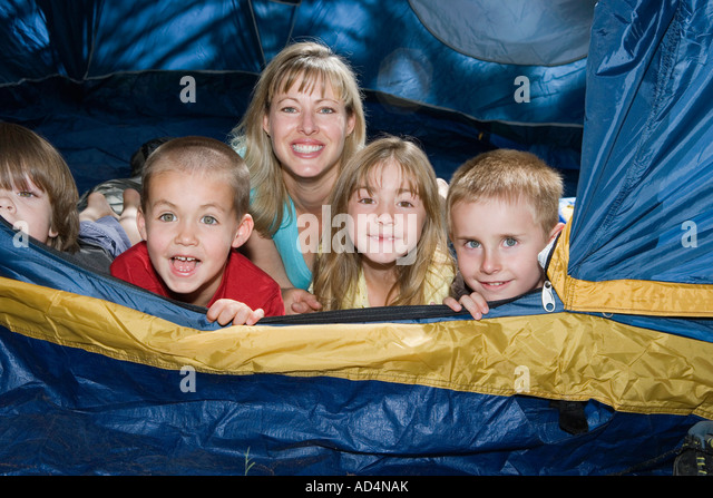 A woman and a group of children lying down in a tent - Stock-Bilder