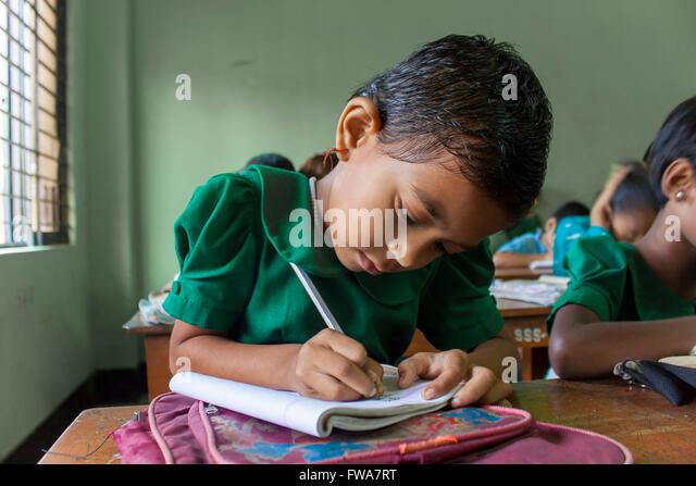 A little Girl writing rural primary school classroom in SSS (Society for Social Service) Center, Tangail, Dhaka - Stock-Bilder