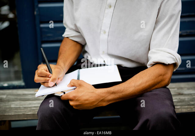 Man writing in notebook - Stock Image