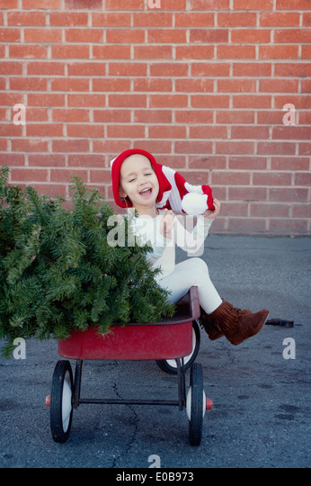 Girl sitting in trailer with christmas tree - Stock Image