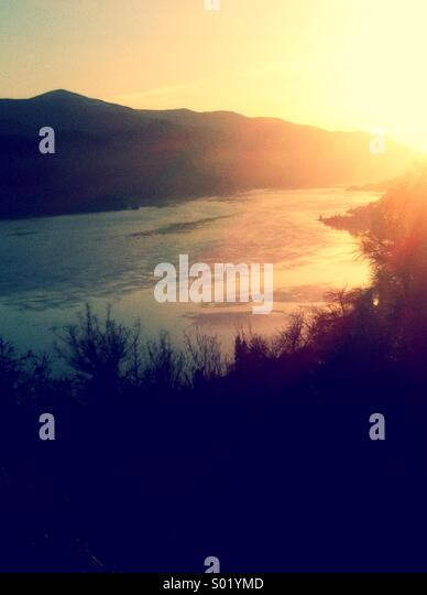 Sunset in valley with river between hillsides - Stock Image