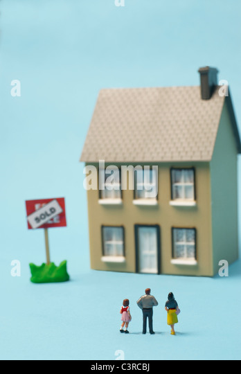 Model figures in front of model house - Stock Image