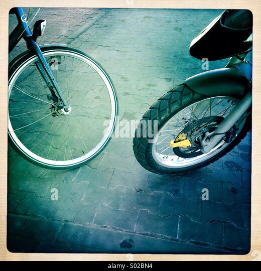 A bike and a motorcycle are seen parked accross from each other. - Stock Image