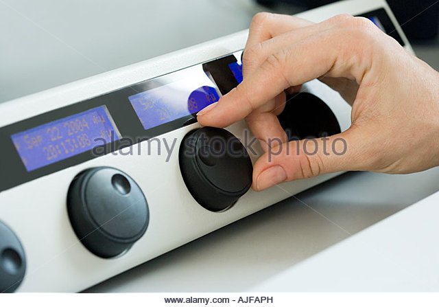 A scientist turning a dial - Stock Image
