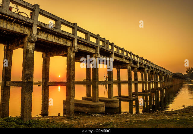 Sunset over the historic wooden U Bein Bridge near Mandalay in Myanmar. Long exposure. - Stock Image