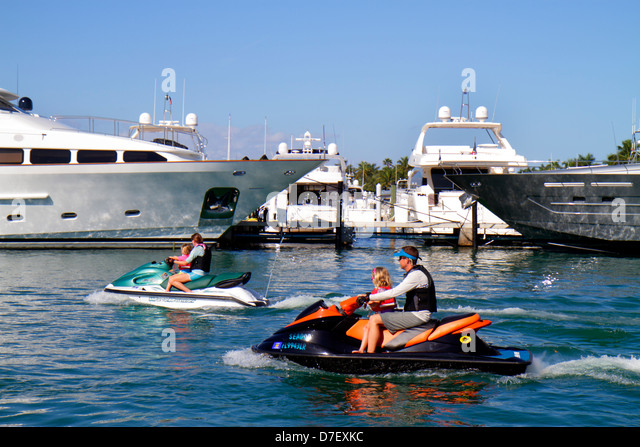 Miami Beach Florida Biscayne Bay marina boats yachts jet ski wave runner man woman mother father children girl rental - Stock Image