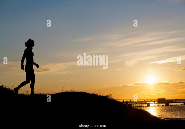 Full length of silhouette female runner on hill during sunset - Stock Image