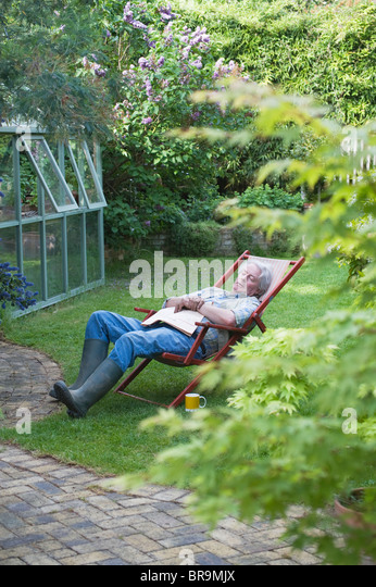 Gardener sleeps on deckchair in back garden - Stock Image