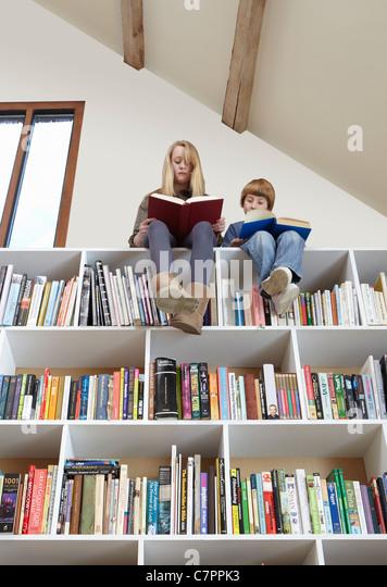 Children sitting on top of bookshelves - Stock Image