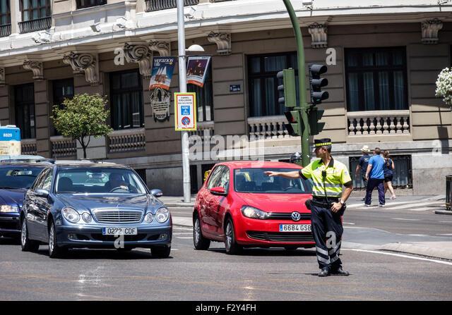Madrid Spain Europe Spanish Centro Calle Gran Via traffic control officer Hispanic man policeman directing - Stock Image