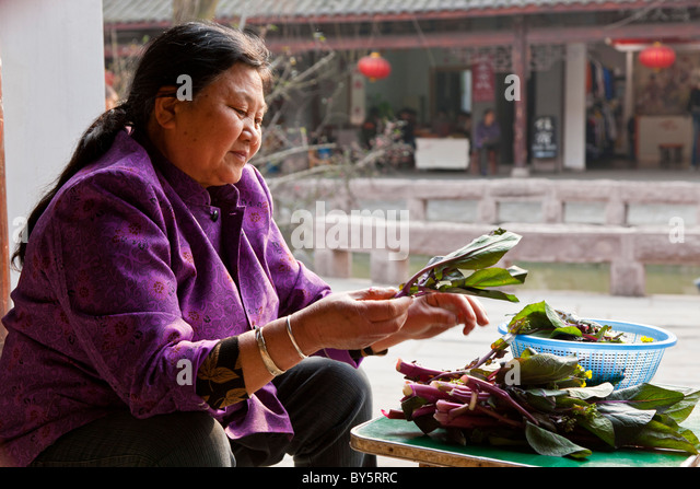 Woman preparing vegetables in the ancient town of Huanglongxi near Chengdu in the Sichuan Province of China. JMH4347 - Stock Image