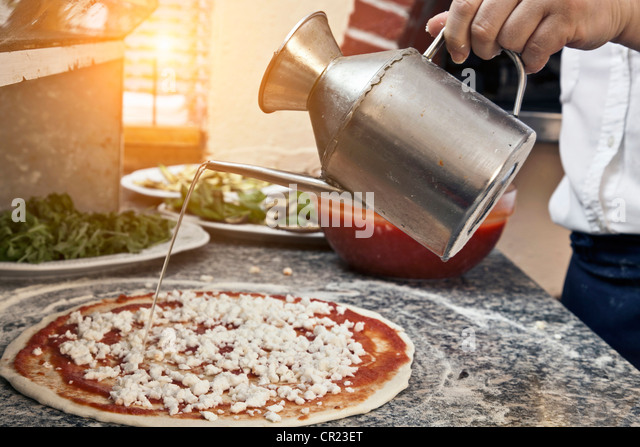 Chef pouring oil on uncooked pizza - Stock Image