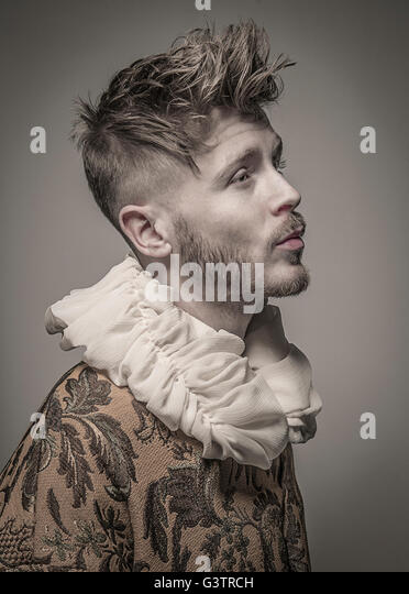 Studio portrait of a young man in profile wearing a jacket with a frilled collar. - Stock-Bilder