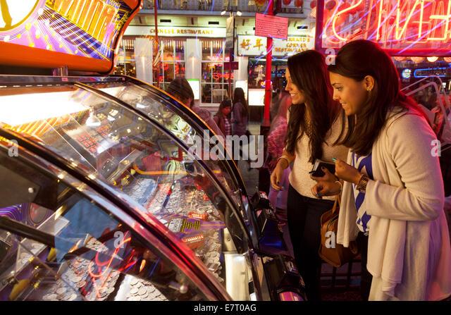 Two women playing gambling games in an amusement arcade, Soho, London UK - Stock Image