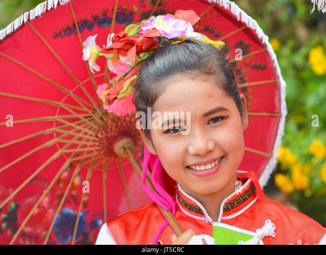 Smiling Thai Chinese Girl in Traditional Dress with Red Parasol (I), Northern Thailand. - Stock Image