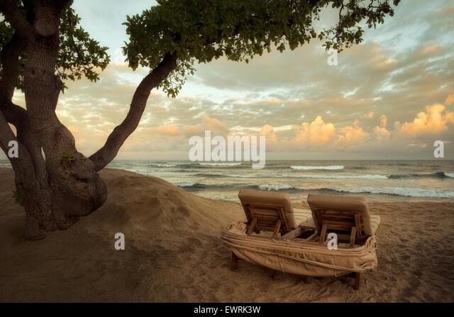 Sunrise and waves with beach chairs. Hawaii, The big Island. - Stock Image