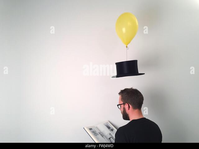 Man Reading Book While Hat Tied To Balloon Over White Background - Stock Image