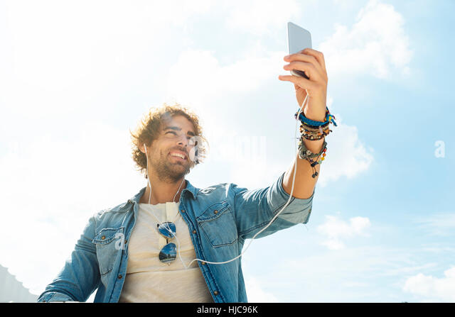 Handsome young man take a picture selfie in the street. - Stock Image