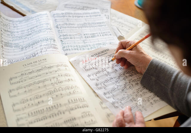 Musician reading    and editing  music scores - Stock Image