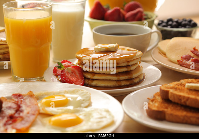 Breakfast pancakes, fruit, eggs, bacon and toast - Stock Image