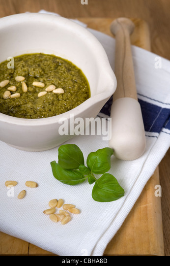 preparing pesto using pine nuts and basil with a pestle and mortar - Stock Image