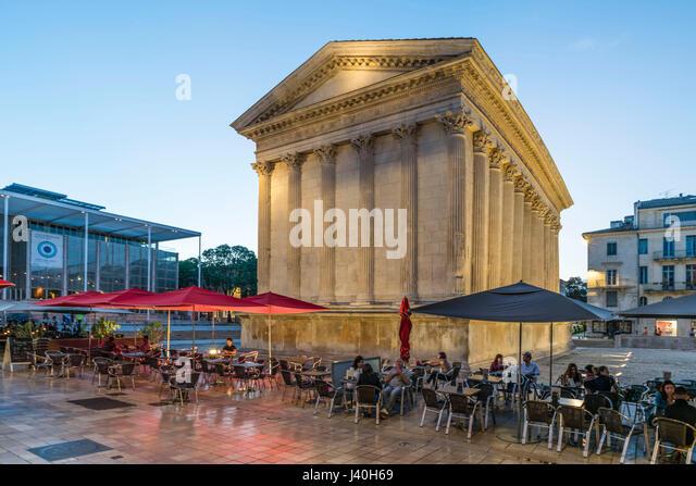 Street Cafe, Maison Carrée , ancient Roman temple , Place de la Maison Carrée, Nîmes, Languedoc-Roussillon, - Stock Image