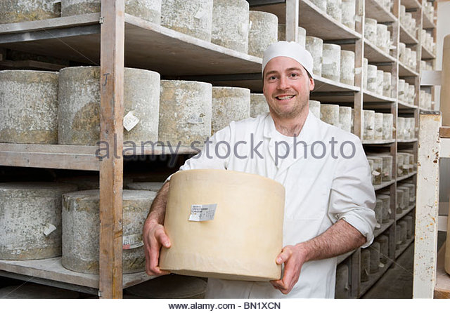 Portrait of smiling cheese maker holding large farmhouse cheddar cheese wheel in cellar - Stock Image