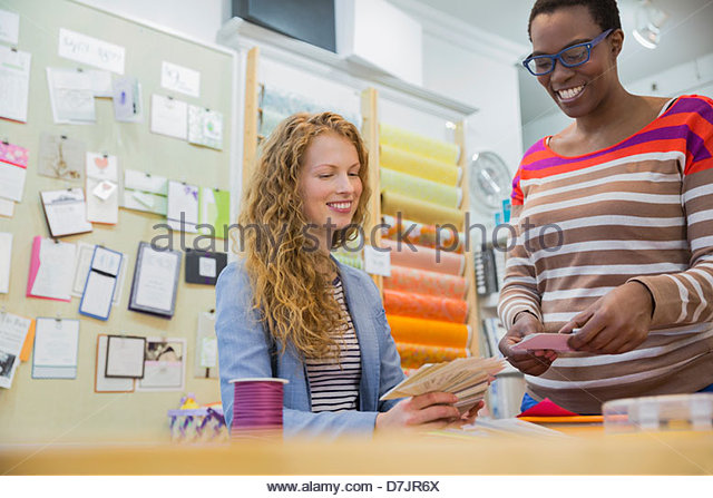 Female small business owner assisting customer with options - Stock Image