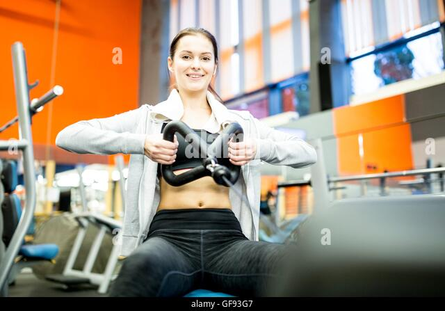 PROPERTY RELEASED. MODEL RELEASED. Portrait of young woman using rowing machine in gym. - Stock Image
