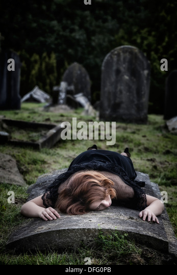 a woman is lying on a tomb - Stock Image