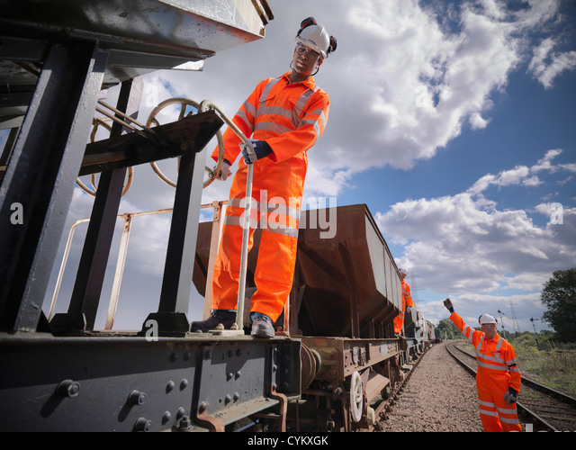 Railway workers standing on train - Stock Image