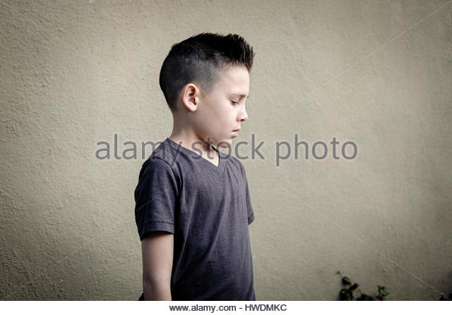 Boy looking down, wall in background - Stock-Bilder