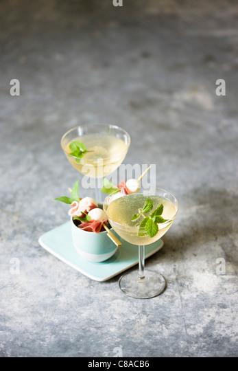 Raw ham and mozzarella mini brochettes and glasses of white wine - Stock Image