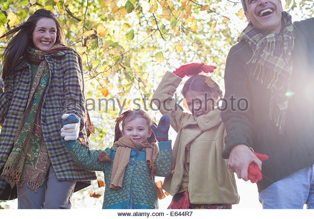 Family laughing and holding hands outdoors - Stock-Bilder