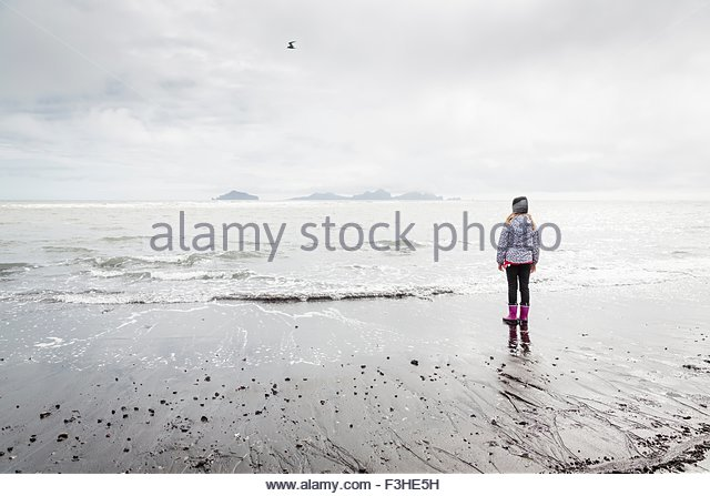 Young girl, standing on beach, looking at view, rear view, Landeyjahofn, Iceland - Stock Image