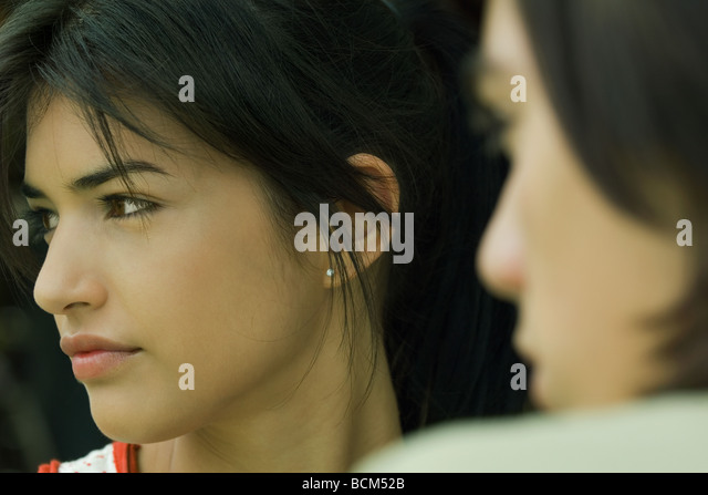 Young woman looking away, teen boy in foreground, cropped view - Stock Image
