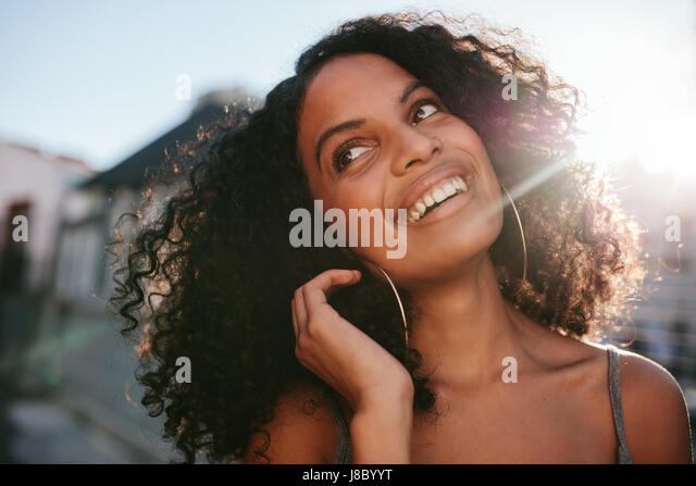 Close up portrait of young african woman with curly hair looking away. Afro american female standing outdoors and - Stock Image