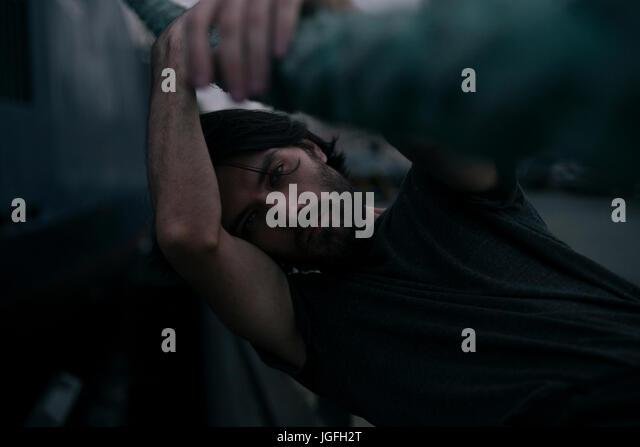 Depressed Caucasian man holding thick rope - Stock Image