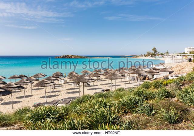 Beach umbrellas on Nissi Beach at the Nissi Beach Resort in Agia Napa, Cyprus - Stock Image