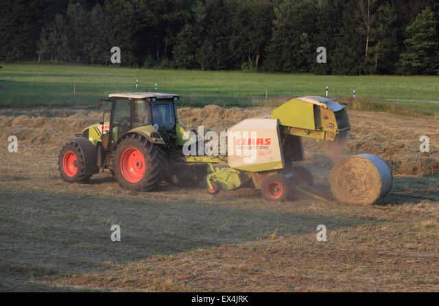 Farmer on tractor collecting and baling hay in round bales. Bavaria, Germany, Europe.  Photo by Willy Matheisl - Stock Image