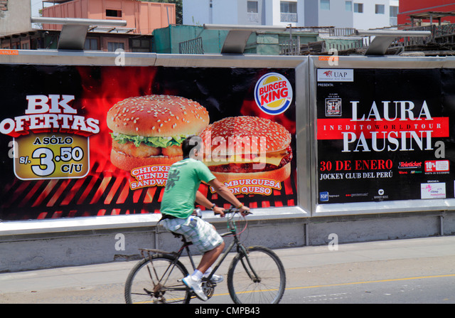 Lima Peru Miraflores Avenida Armendariz street scene Hispanic man bicycle pedaling billboard ad marketing Burger - Stock Image