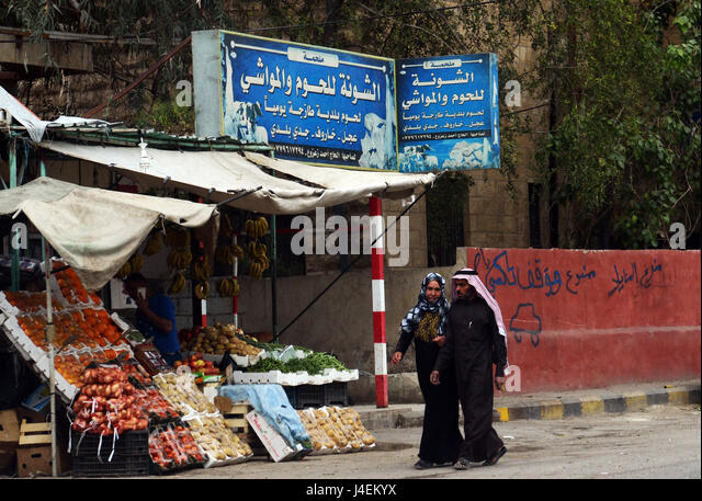A Jordanian couple walking by a vegetable store in a small town in Jordan's Jordan valley. - Stock Image