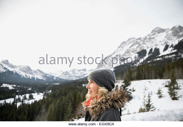 Woman in warm clothing below snowy mountains - Stock Image