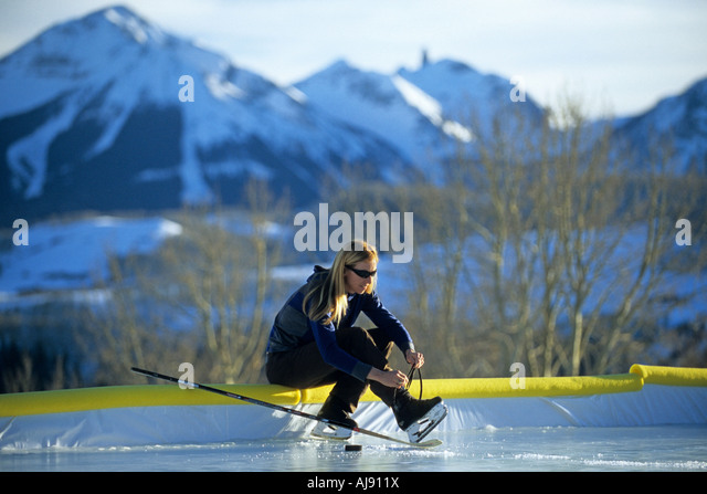 Woman putting on ice skates. - Stock Image
