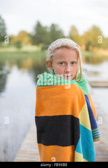 Sweden, Smaland, Braarpasjon, Portrait of girl (10-11) wrapped in towel after swimming in lake - Stock Image