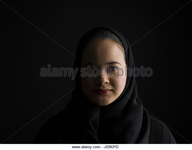 Portrait serious Middle Eastern woman wearing black hijab in shadow against black background - Stock Image